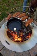 steaks grilling on outpost grate over stainless steel zentro fire pit