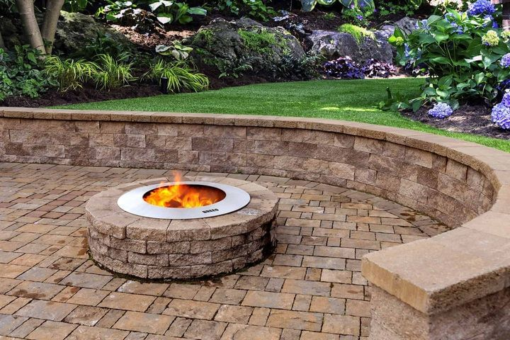 Breeo stainless steel zentro smokeless fire pit insert with block surround on paver patio