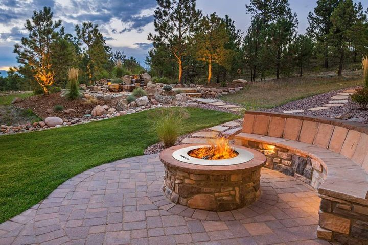 stainless steel zentro smokeless fire pit insert in stone masonry fire pit on outdoor patio