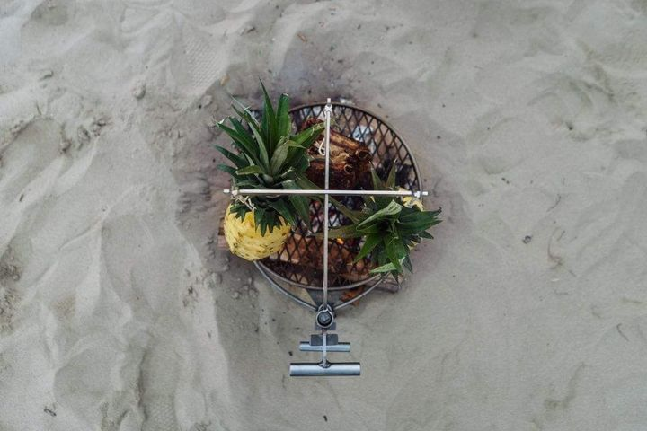 Top-down shot of the Kettle Hook with meat and pineapple hanging from it over the Outpost at the beach.