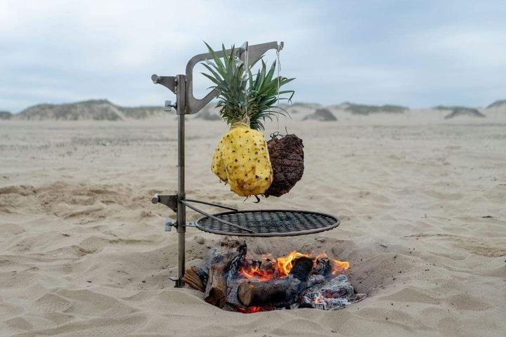 Outpost grill over a beach campfire with meat and pineapple hanging from the kettle hook.