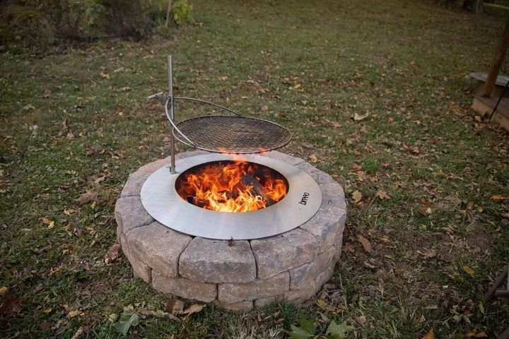 stainless steel zentro smokeless fire pit insert with outpost grate in backyard