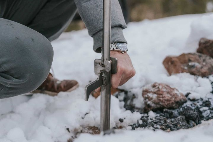 Man wearing a watch putting the Outpost Anchorpoint in snow-covered ground