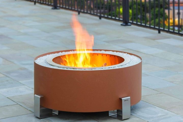 Earth Rust Luxeve smokeless fire pit on a patio with fencing in background