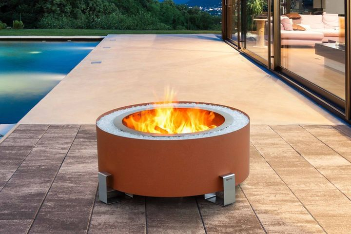 Earth rust Luxeve smokeless fire pit on a patio beside a pool on left with a glass wall showing a living room on right