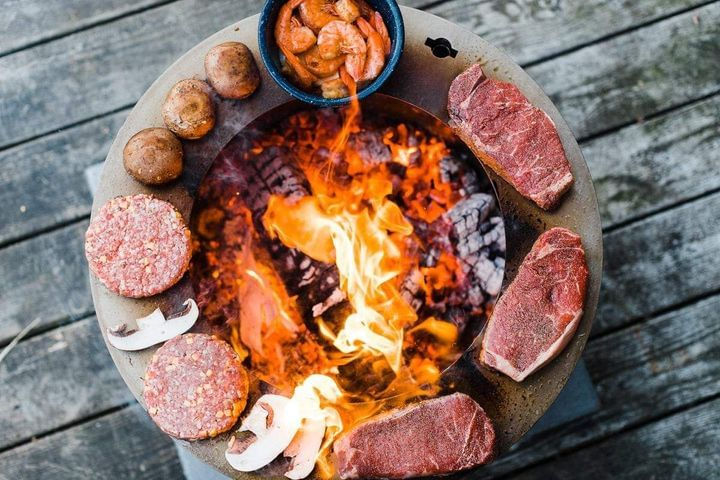 Steak, mushrooms, and shrimp grilling on the SearPlate rim of X Series 19 smokeless fire pit