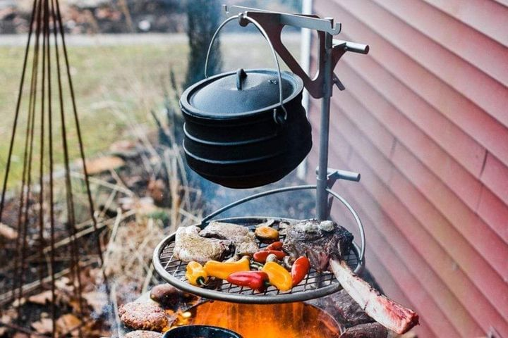 Kettle Hook holding a kettle over a smokeless fire pit with meat and peppers cooking on the Outpost grill attachment