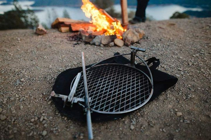 Campfire by a river with the Outpost grilling system in front of it laying on the bag.