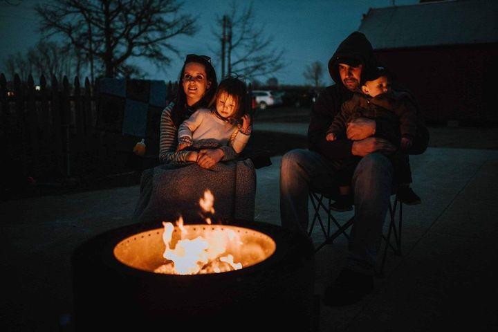 Mother holding daughter on lap and father holding son sitting beside a Luxeve smokeless fire pit.