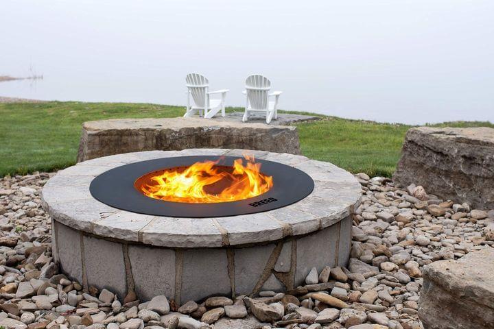 Breeo black zentro smokeless fire pit insert with masonry surround next to lake