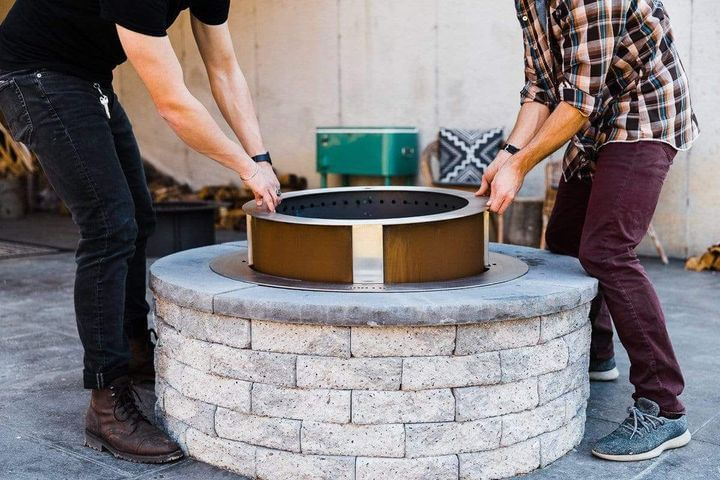 X Series 24 smokeless fire pit being inserted into insert ring and block surround by two men
