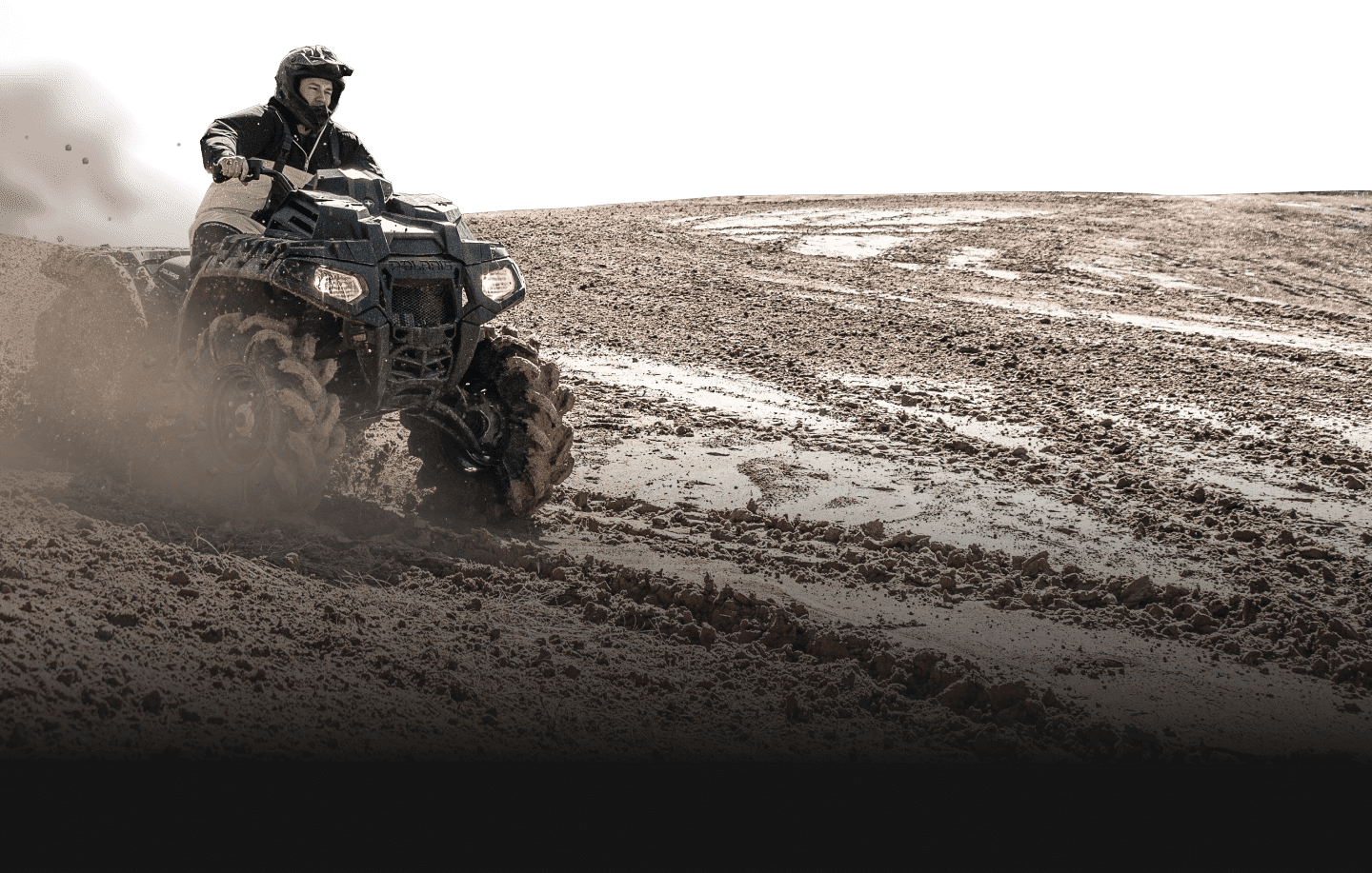 Man riding an ATV in the mud