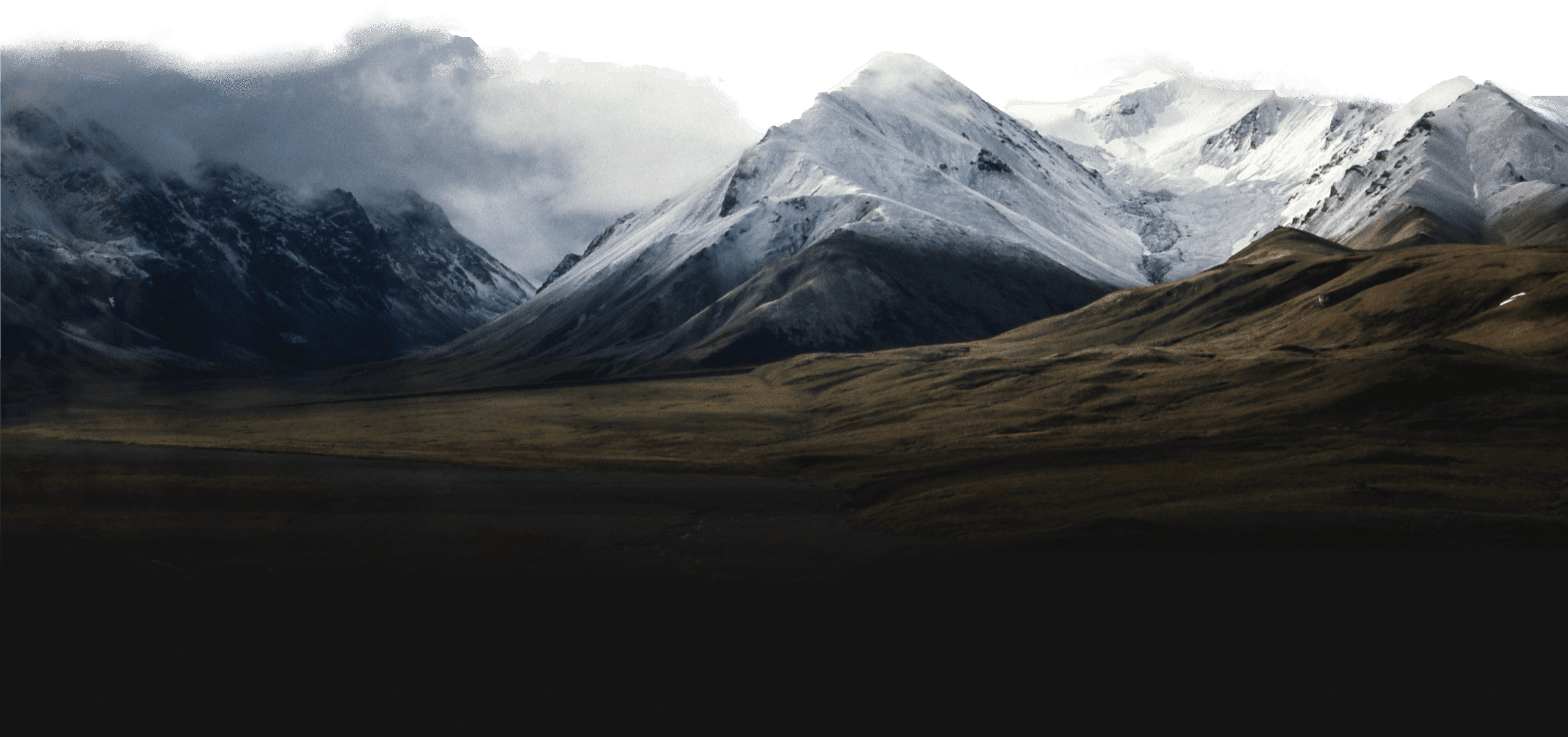 Rolling hills leading into snow capped mountains