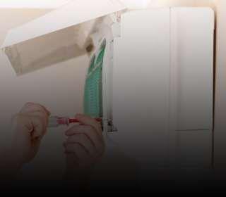 Pessoa desparafusando peças do ar-condicionado com uma chave de fenda