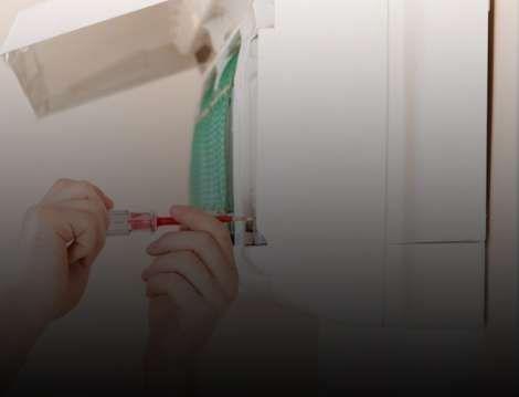 Ar-condicionado sendo instalado por uma pessoa com chave de fenda em mãos