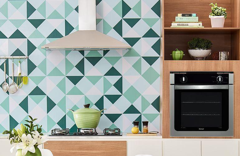 cozinha com móveis embutidos em detalhes de madeira e branco com cooktop preto, coifa de inox e forno de embutir da Consul.