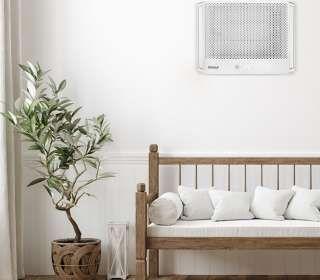 ambiente com sofá, vaso e ar-condicionado