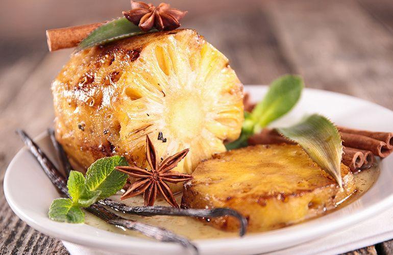 sobremesa de natal abacaxi assado na canela em prato decorado com folhas e canela