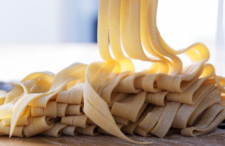 Massa de macarrão fresca polvilhada com farinha de trigo em cima de uma bancada.