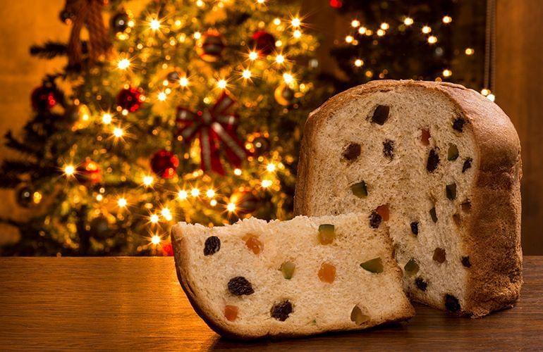receita de panetone tradicional cristalizado para o natal na mesa com árvore de fundo