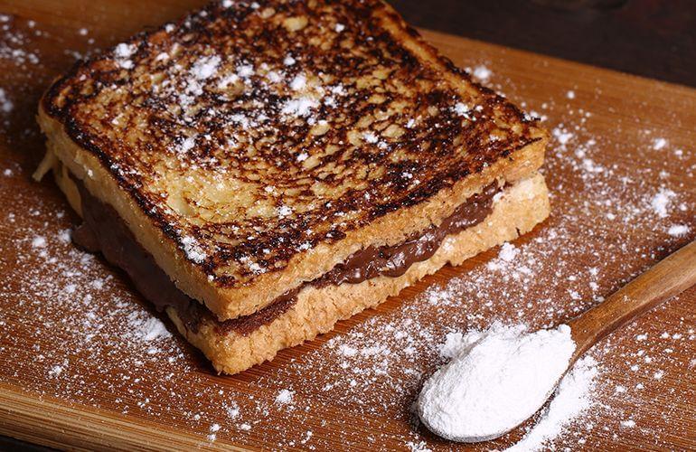 Rabanada recheada com nutella com uma colher para polvilhar de açúcar
