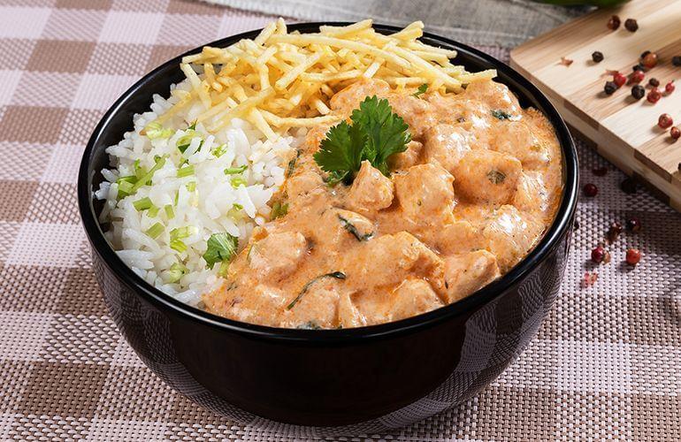 Strogonoff de frango em um bowl preto com batata palha e arroz.