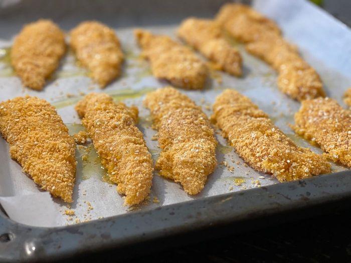זילוף שמן זית להכנת שניצל פריך ועסיסי אפוי בתנור